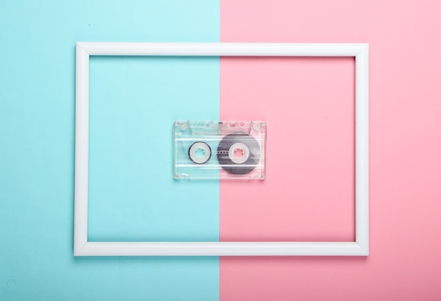 Audio cassette on pink blue pastel surface with white frame