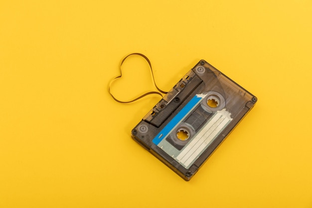 黄色の背景にオーディオカセットテープ。ハートを形作るフィルム、バレンタインポストカード。空きスペース。