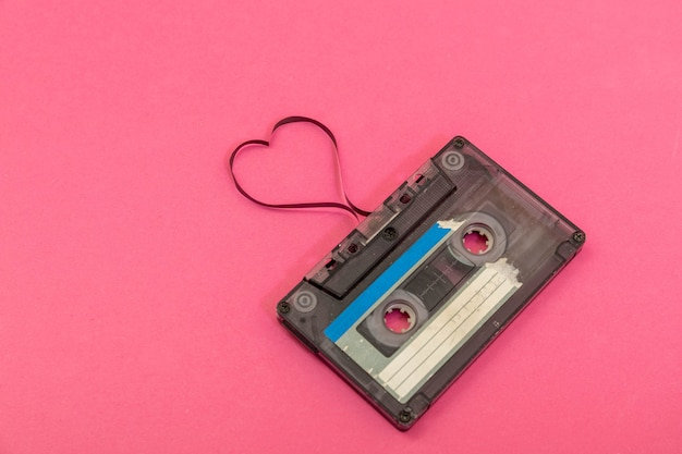 Audio cassette tape on rose background. film shaping heart, valentine postcard. empty space.