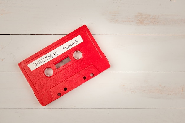 白い木製のテーブルにクリスマスソングとオーディオカセットテープ