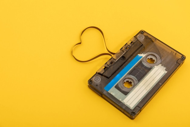 Audio cassette tape on yellow background. film shaping heart, valentine postcard. empty space.