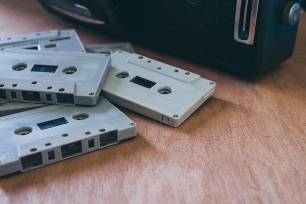 Audio cassette tapes with cassette player on wooden table