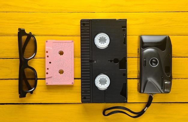 オーディオカセット、vhs、3 dメガネ、黄色の木製の背景に流行に敏感なフィルムカメラ。 80年代からのレトロなデバイス。上面図。