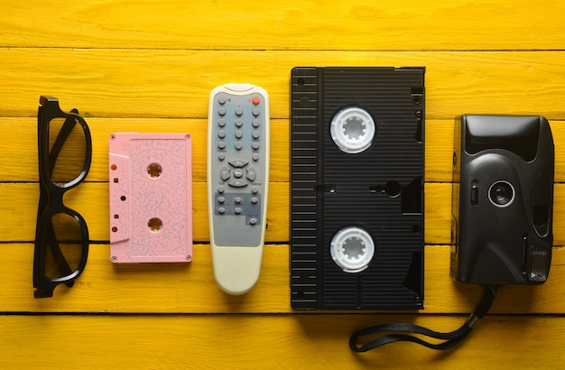 Audio cassette, vhs, 3d glasses, tv remote, hipster film camera on a yellow wooden background. retro devices from 80s. top view.