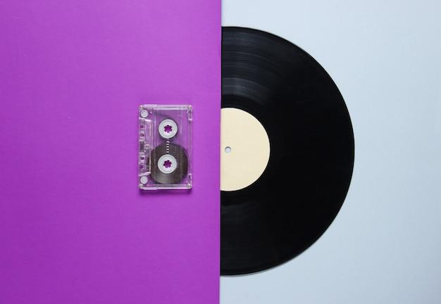 Audio cassette, vinyl record on a purple gray table. retro style. top view