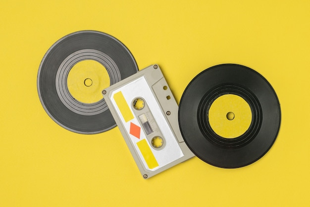 Audio cassette with magnetic tape and vinyl discs on yellow. retro devices for storing and playing audio recordings.