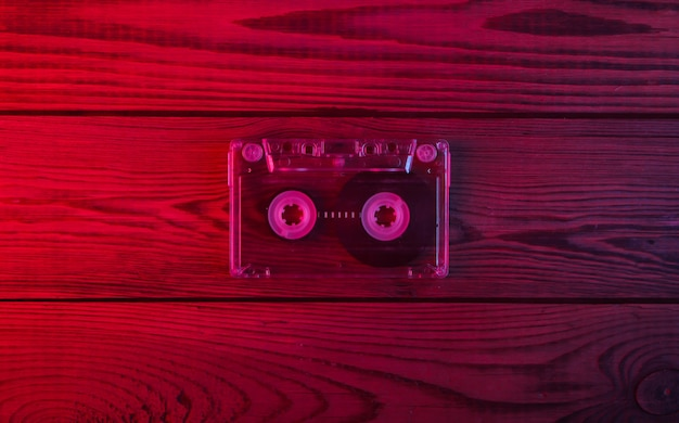 Audio cassette on wooden surface. neon red and blue light