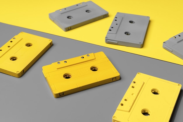 Audio cassettes on gray and yellow background top view copy space