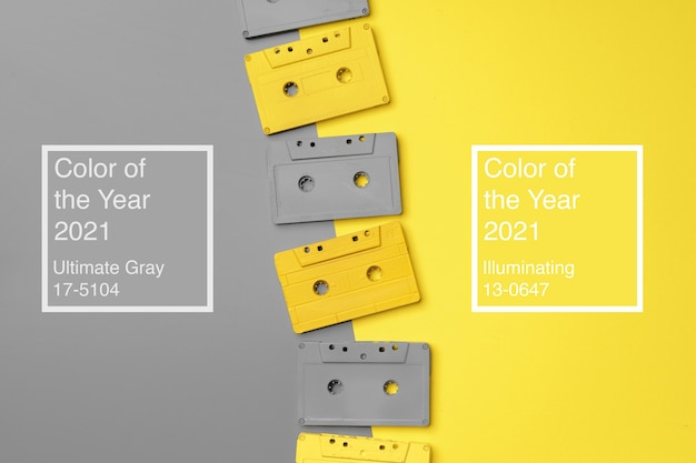 Audio cassettes on gray and yellow background top view