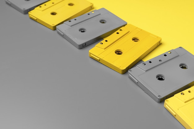 Audio cassettes on gray and yellow top view copy space