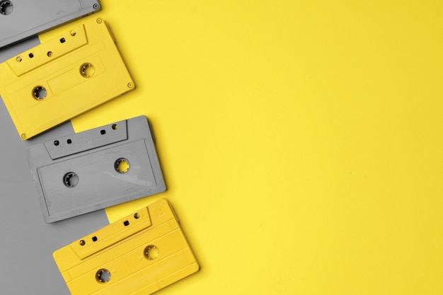 Audio cassettes on gray and yellow top view