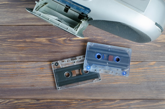 Audio cassettes and a tape recorder on wooden background