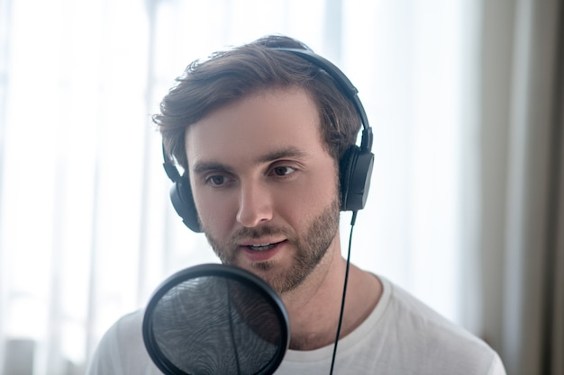 Audio conference. young bearded man sitting in headphones and having an audio conference