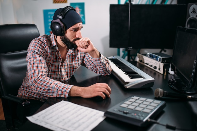 Audio engineer in headphones work with musical keyboard in studio. professional digital sound record technology