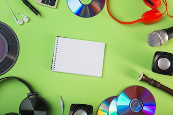 Audio equipments around the spiral blank notepad on green background