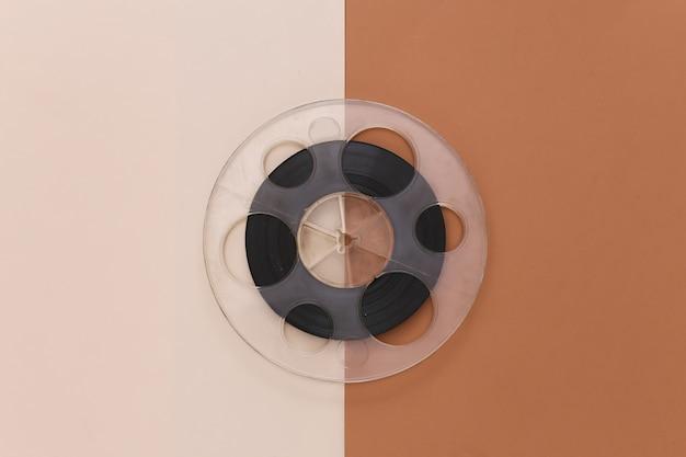Audio magnetic tape. film reel on brown beige. retro style