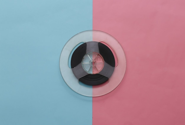 Audio magnetic tape. film reel on pink blue pastel. retro style. minimalism