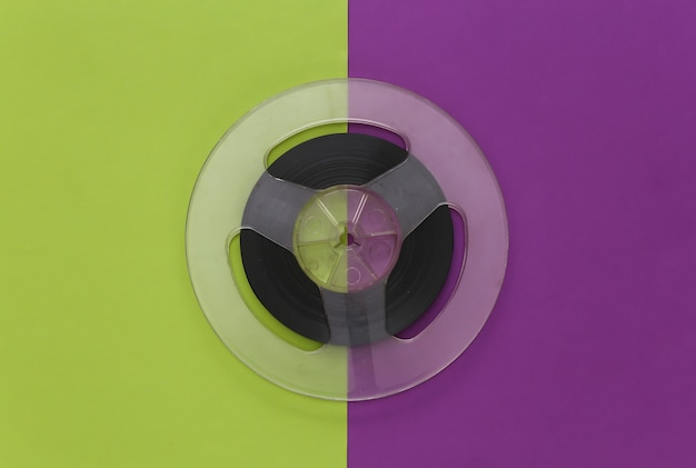 Audio magnetic tape. film reel on a purple green. retro style