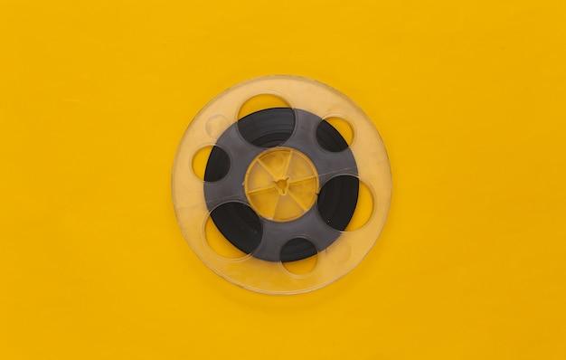 Audio magnetic tape. film reel on yellow. retro style