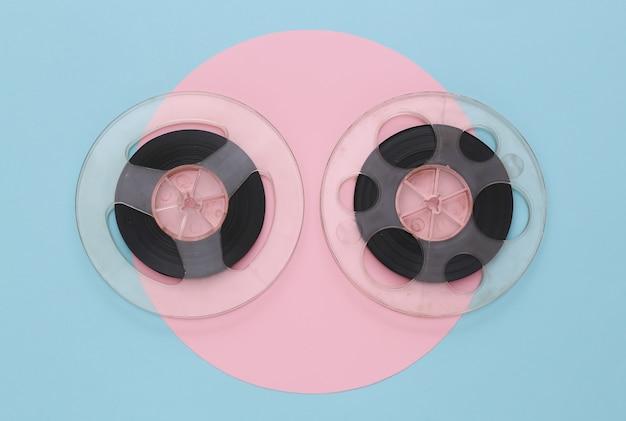 Audio magnetic tape. two film reel on pink blue pastel. retro style. minimalism