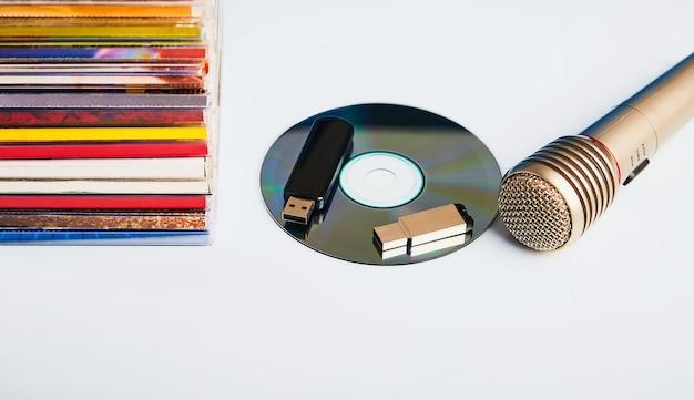 나무 테이블에 cd와 플래시 드라이브가있는 오디오 마이크