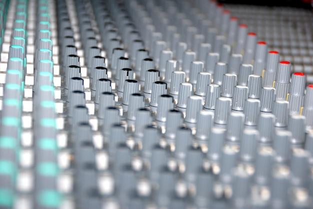レコーディングスタジオのオーディオミキシングコンソール。サウンドミキサーのフェーダーとノブ。