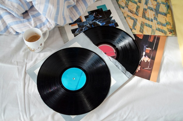 Audio retro gramophone vinyl sound records and music album on bed sheet with coffee cup.