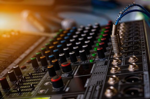 흐릿한 배경의 사운드 제어실에서 오디오 사운드 믹서 아날로그
