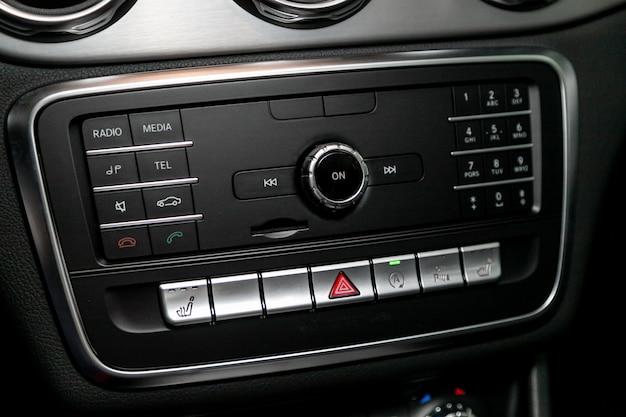 Аудио стереосистема, панель управления и компакт-диск в современном автомобиле. панель управления аудиоплеером и другими устройствами