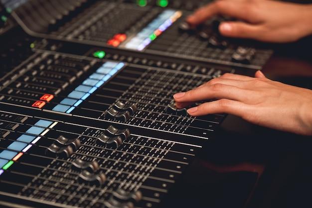 Аудиосистема для профессионалов. крупный план звукорежиссера, регулирующего цифровой микшерный пульт. студия звукозаписи. студия медиа-производства. музыкальный сервис