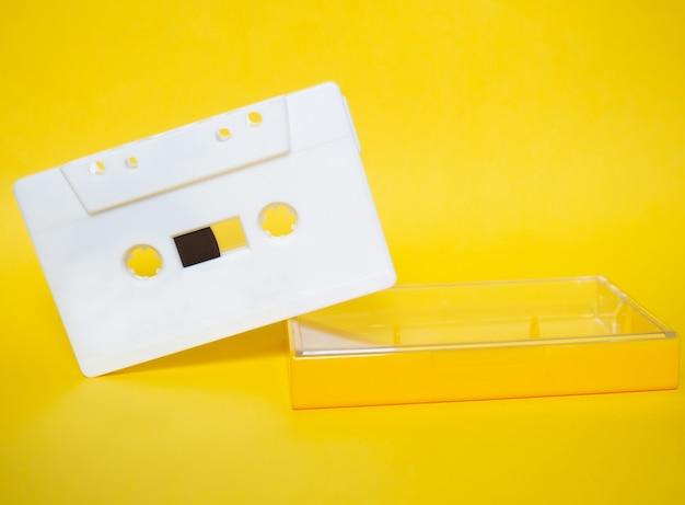 오디오 테이프. 노란색 배경의 빈티지 흰색 오디오 테이프입니다. 프리미엄 사진