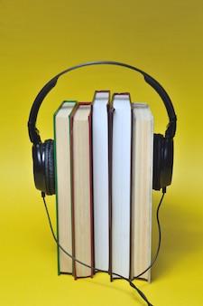 オーディオブックのコンセプト。ヘッドホンをつけた本の山。閉じる