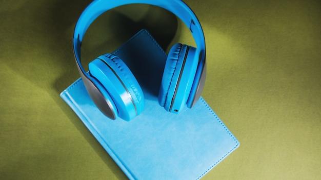 Концепция аудиокниги. книга и наушники на деревянном столе