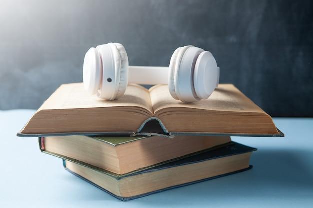 Концепция аудиокниги. книги и наушники на столе