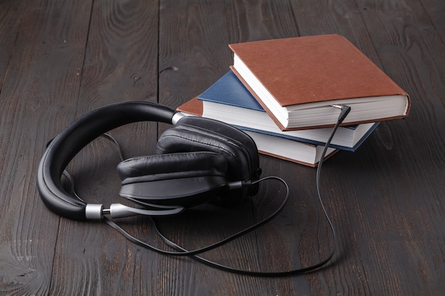 Audiobook concept with headphone and paper book on table