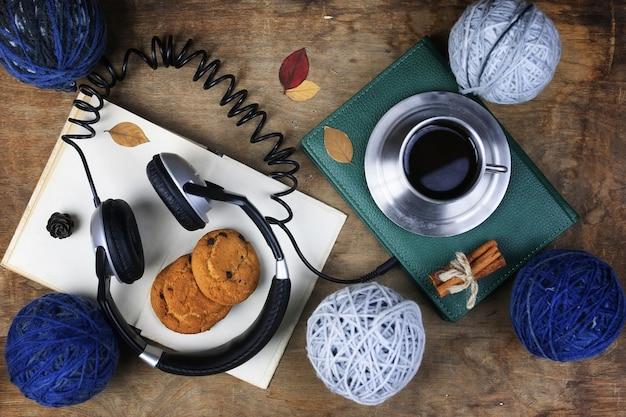 Аудиокнига наушники и книга на деревянном столе
