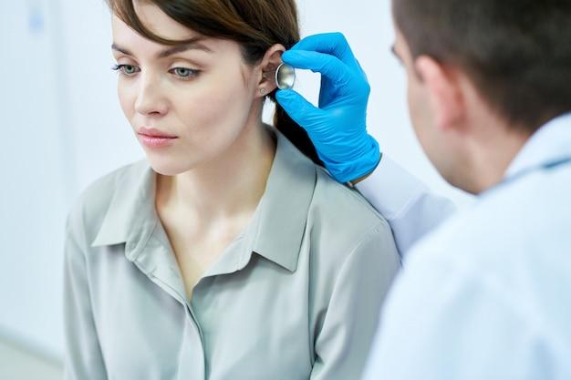 Аудиолог осматривает пациента