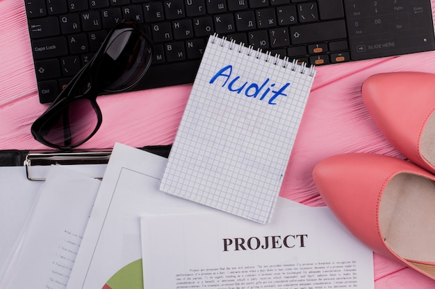 Audit text on notepad with womens accessories on office pink desk