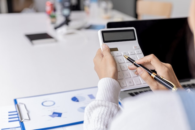 The auditor is pressing the white calculator, she is the company's auditor is responsible for checking all the company's income and expenses documents for accuracy. accounting audit concept.