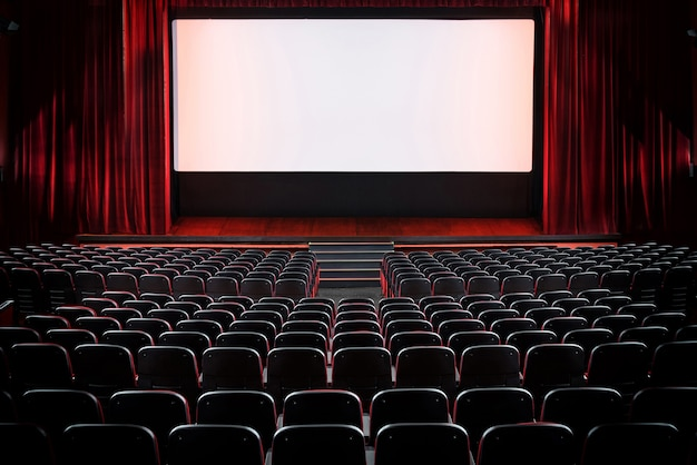 Auditorium of an empty movie theatre and stage with opened red velvet curtains
