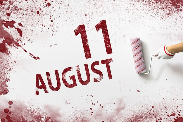 August 11st . day 11 of month, calendar date. the hand holds a roller with red paint and writes a calendar date on a white background. summer month, day of the year concept.