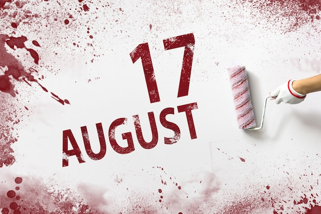 August 17th. day 17 of month, calendar date. the hand holds a roller with red paint and writes a calendar date on a white background. summer month, day of the year concept.