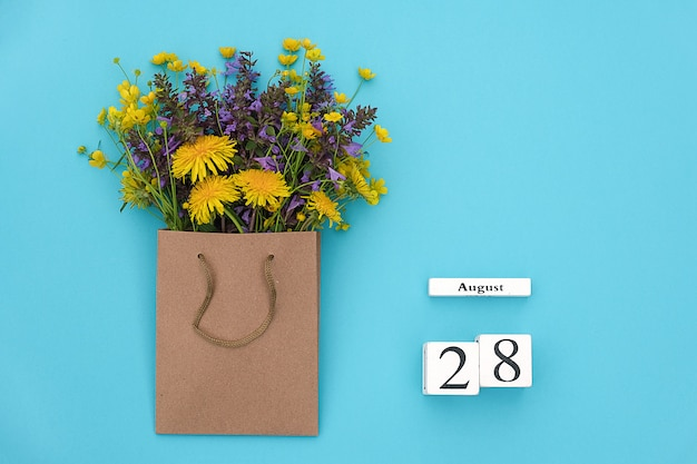 August 28 and field colorful flowers in craft package on blue background. greeting card