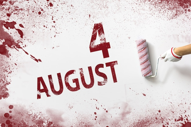 August 4th. day 4 of month, calendar date. the hand holds a roller with red paint and writes a calendar date on a white background. summer month, day of the year concept.