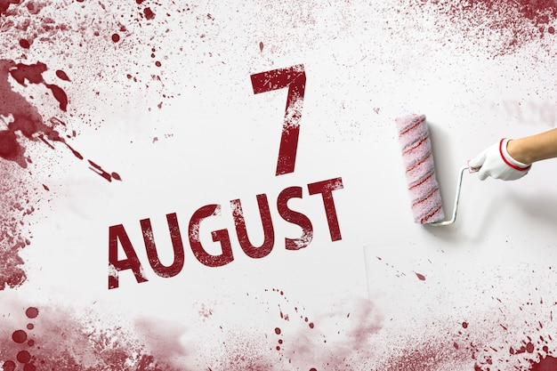 August 7th. day 7 of month, calendar date. the hand holds a roller with red paint and writes a calendar date on a white background. summer month, day of the year concept.
