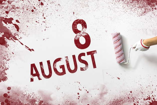 August 8th. day 8 of month, calendar date. the hand holds a roller with red paint and writes a calendar date on a white background. summer month, day of the year concept.