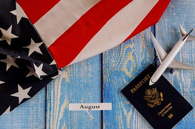Август месяц календарного года, путешествия, туризм, эмиграция в сша. американский флаг с паспортом сша и модель самолета пассажира.