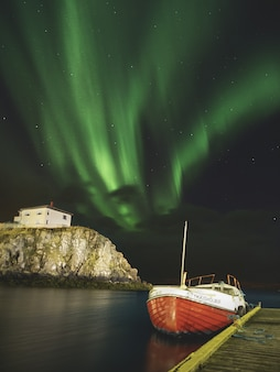 Aurora borealis above a boat at the dock in iceland