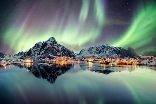 ノルウェー、ロフォーテン諸島、レーヌの漁村の山で踊るオーロラ