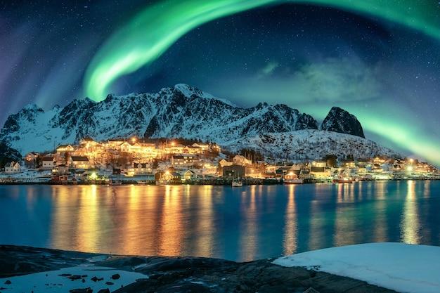 Aurora borealis over fishing village illumination on coastline in winter at lofoten islands, norway